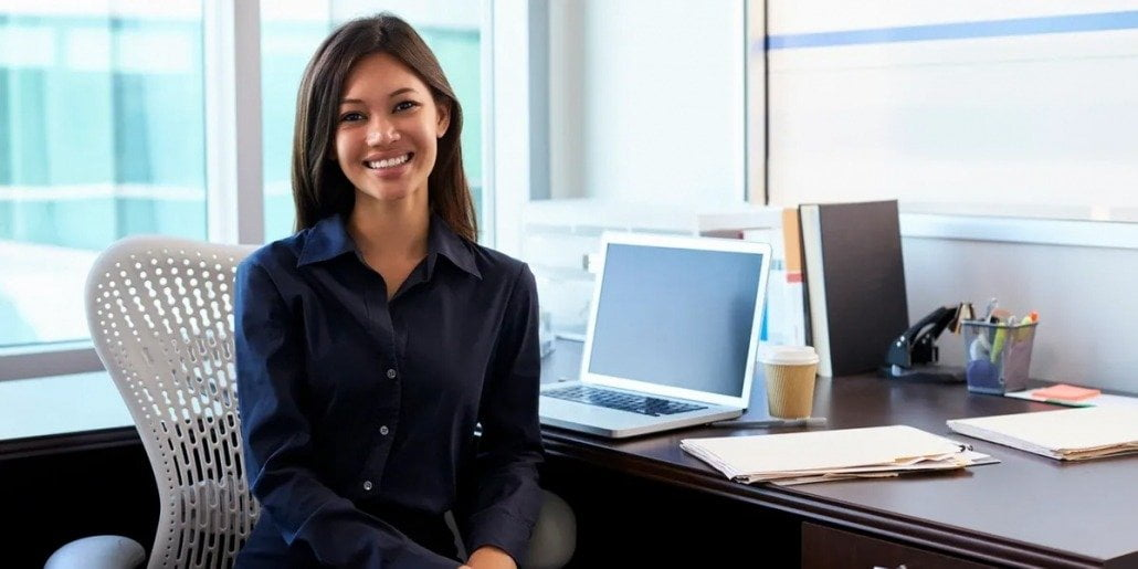 woman sitting at her desk with her laptop in the background smiling