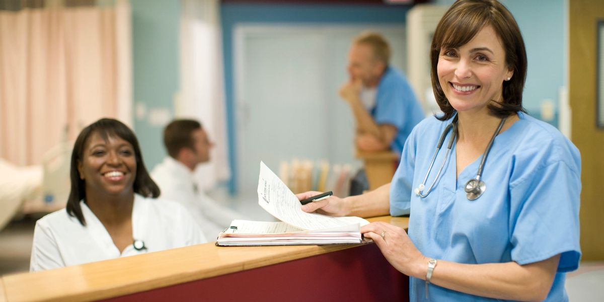 hospital workers wearing scrubs standing at desk with papers with other hospital workers in background